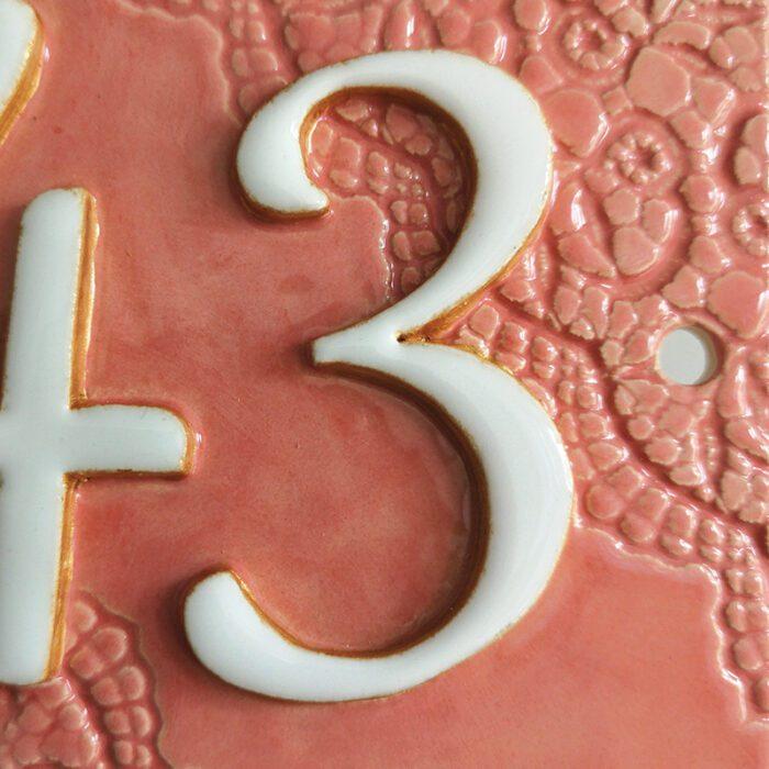Detail van handgemaakt keramisch huisnummerbord roze, nummer 43.