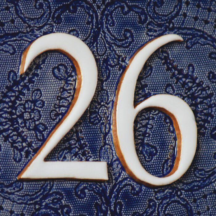 Detail van handgemaakt huisnummer bord met vintage blauwe achtergrond.