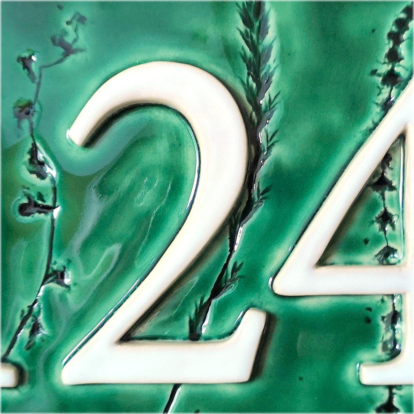 Detail groen huisnummerbord met plantjes.
