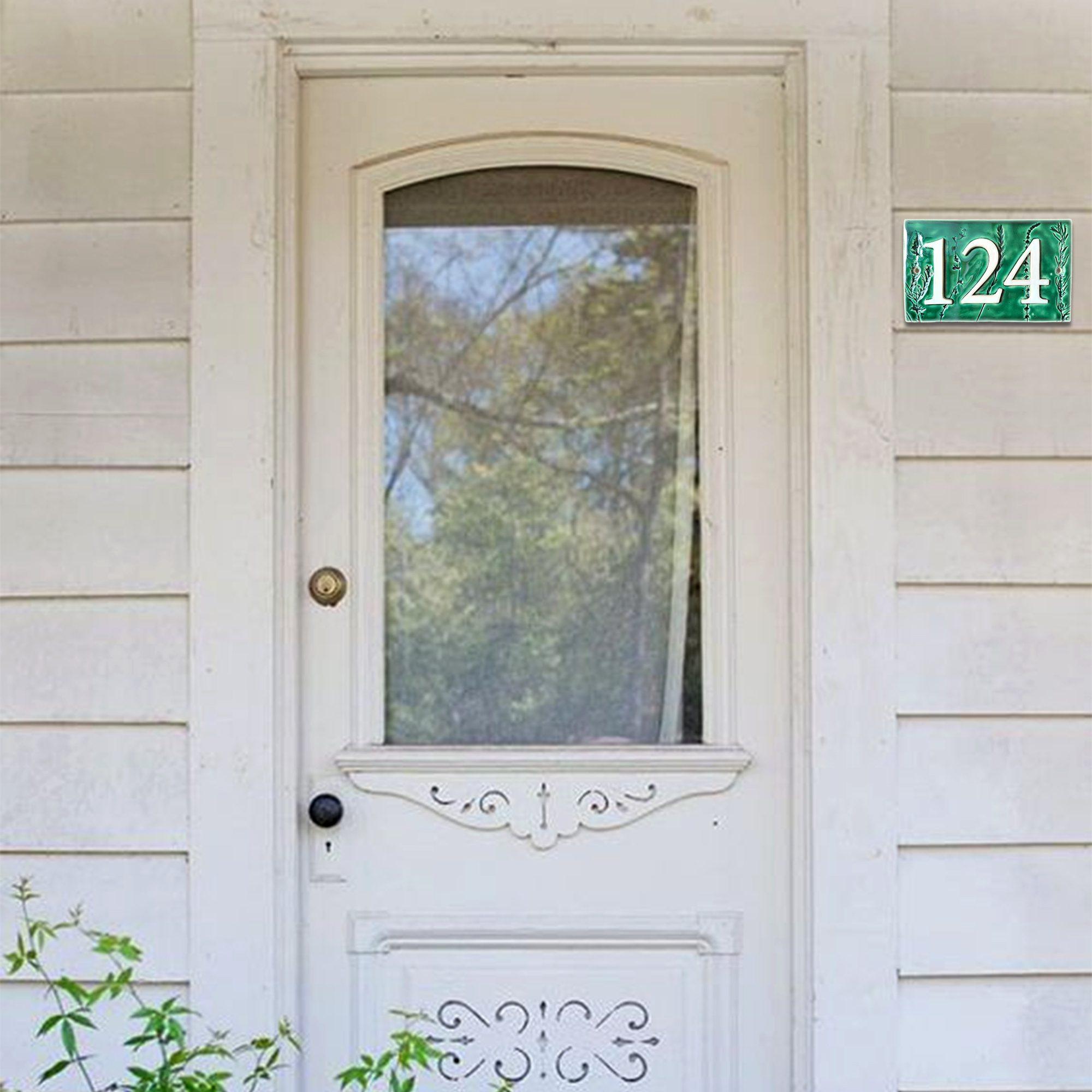 Handgemaakt keramisch huisnummerbord groen, met plantjes bij een deur. Nummer 124.