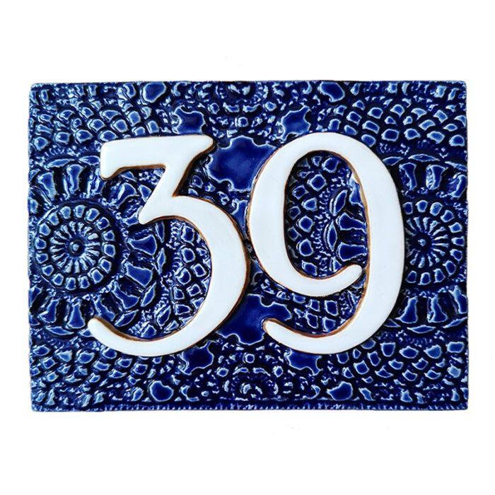 Handgemaakt keramisch huisnummerbord blauw, nummer 39. Gedecoreerd met een gehaakt kleedje