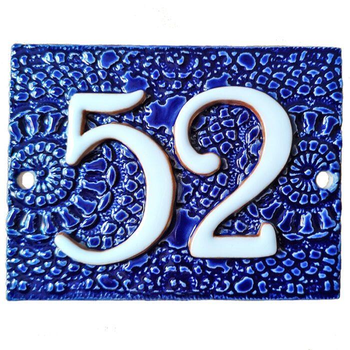 Handgemaakt keramisch huisnummerbord blauw, nummer 52. Gedecoreerd met een gehaakt kleedje