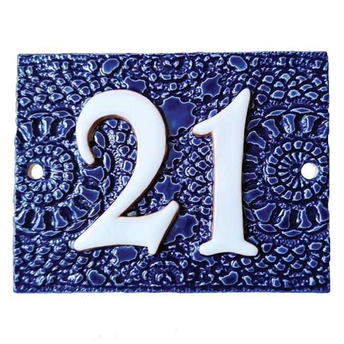 Handgemaakt keramisch huisnummerbord blauw, nummer 21. Gedecoreerd met een gehaakt kleedje.
