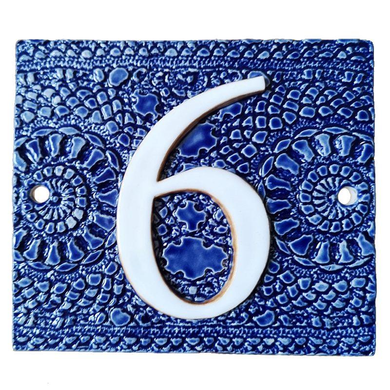 Huisnummer 6 in blauw met afdruk van een gehaakt kleedje als achtergrond