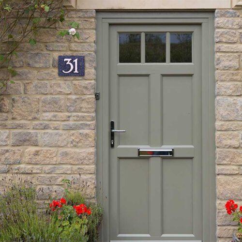 Handgemaakt keramisch huisnummerbord blauw, nummer 31. Gedecoreerd met een gehaakt kleedje.